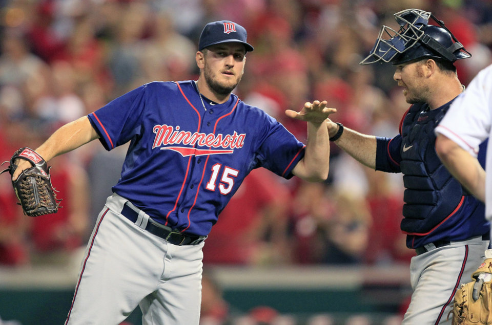 Photo -   Minnesota Twins catcher Ryan Doumit congratulates relief pitcher Glen Perkins (15) after theTwins defeated the Cincinnati Reds 5-4 in a baseball game, Friday, June 22, 2012, in Cincinnati. Doumit hit a home run and Perkins recorded his second save in the game. (AP Photo/Al Behrman)