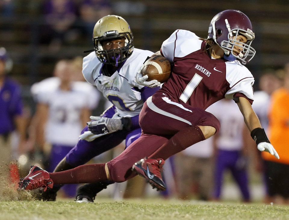 Capitol Hill's Denny Do (1) runs after a catch in front of Chickasha's Lindbergh Cary (9) during a high school football game between Chickasha and Capitol Hill at Star Spencer's Carl Twidwell Stadium in Spencer, Okla., Thursday, Oct. 3, 2013. Photo by Nate Billings, The Oklahoman