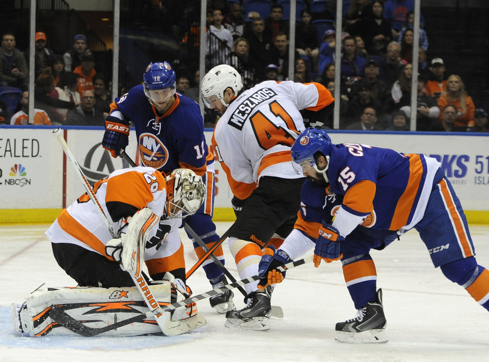 Photo - Philadelphia Flyers goalie Ray Emery (29) and Andrej Meszaros (41) defend against New York Islanders' Josh Bailey (12) and Cal Clutterbuck (15) in the second period of an NHL hockey game on Monday, Jan. 20, 2014, in Uniondale, N.Y. (AP Photo/Kathy Kmonicek)