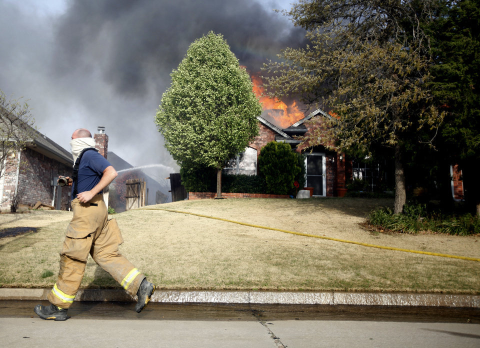 Photo - A firefighter runs past a house as it burns in the Oakwood East Royale neighborhood in Midwest City, Thursday, April 9, 2009. Photo by Bryan Terry, The Oklahoman