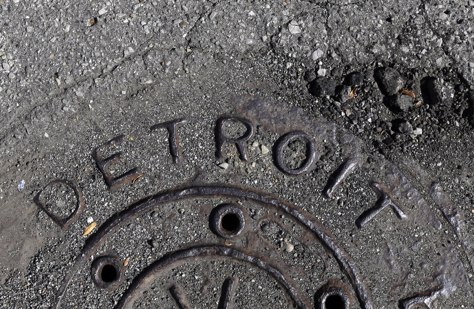 Photo - FILE - In an Oct. 10, 2013 photo is a manhole cover is seen in Detroit. The city, which was about to default on a good chunk of a long-term debt exceeding $18 billion, now is getting a second chance in a federal bankruptcy court-led restructuring. (AP Photo/Carlos Osorio, File)