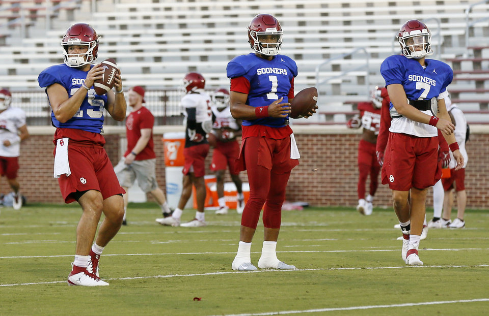 Photo - From left, OU quarterbacks Tanner Mordecai (15), Jalen Hurts (1) and Spencer Rattler (7) stand near each other during a passing drill at football practice for the University of Oklahoma Sooners at Gaylord Family - Oklahoma Memorial Stadium in Norman, Okla., Monday, Aug. 12, 2019. [Nate Billings/The Oklahoman]