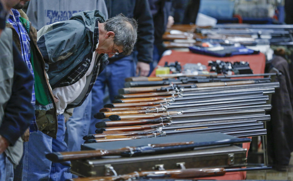 FILE - In this Jan. 26, 2013 file photo, a customer looks over shotguns on display at the annual New York State Arms Collectors Association Albany Gun Show at the Empire State Plaza Convention Center in Albany, N.Y.  A bipartisan quartet of senators, including two National Rifle Association members and two with �F� ratings from the potent firearms lobby, are quietly trying to reach compromise on expanding the requirement for gun-sale background checks. (AP Photo/Philip Kamrass, File)