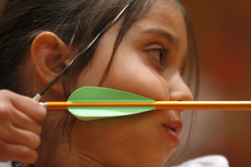 Photo - Eileen Kavariti, 9, pulls back her bow during an after-school archery class for students ages 8 to 17.