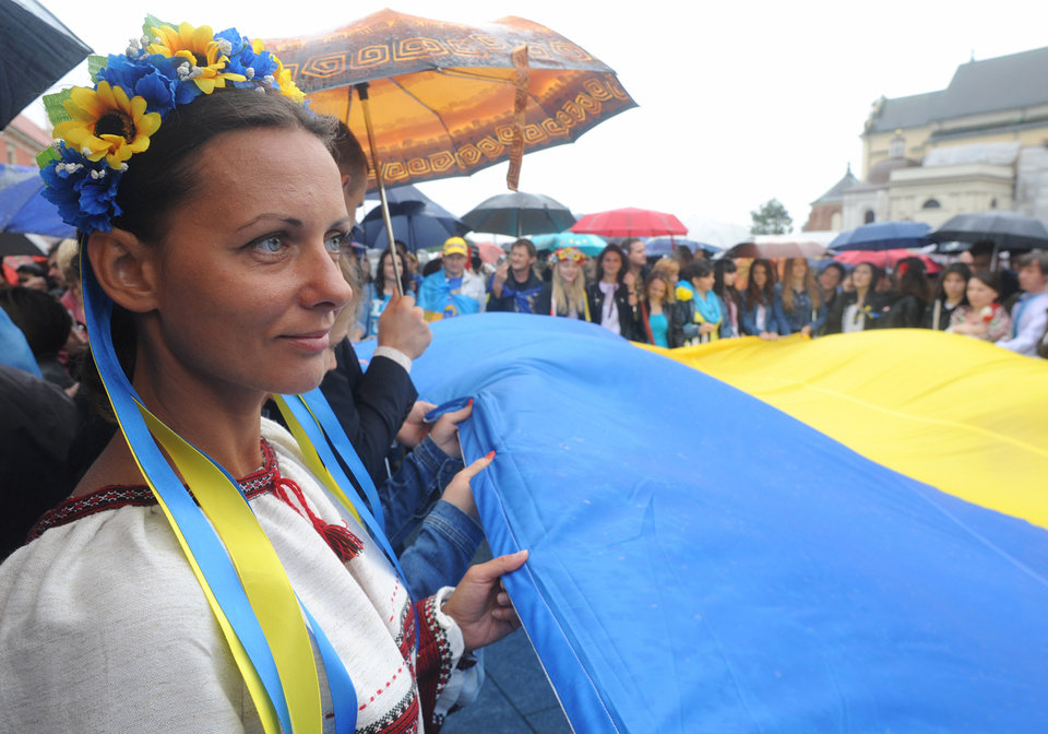 Photo - Ukrainians living in Poland hold their national flag during celebrations marking the 23. anniversary of Ukraine's independence, in Warsaw, Poland, Sunday, Aug. 24, 2014. (AP Photo/Alik Keplicz)