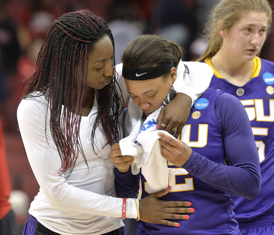 Photo - LSU assistant coach Tasha Butts, left, embraces Danielle Ballard following their loss to Louisville in a regional semifinal game at the NCAA women's college basketball tournament, Sunday, March 30, 2014, in Louisville, Ky. Louisville defeated LSU 73-47. (AP Photo/Timothy D. Easley)