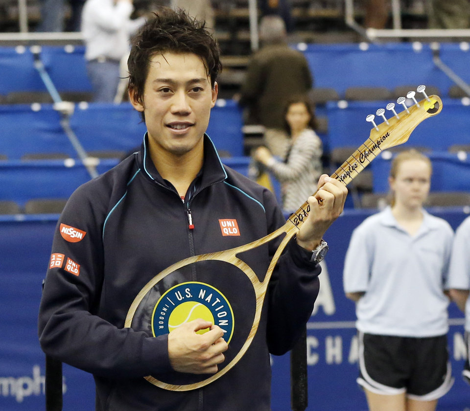 Photo - Kei Nishikori, of Japan, holds the winner's trophy after defeating Ivo Karlovic, of Croatia, 6-4, 7-6 (0) in the singles final at the U.S. National Indoor Tennis Championships, Sunday, Feb. 16, 2014, in Memphis, Tenn. The trophy is shaped like a guitar. (AP Photo/Rogelio V. Solis)