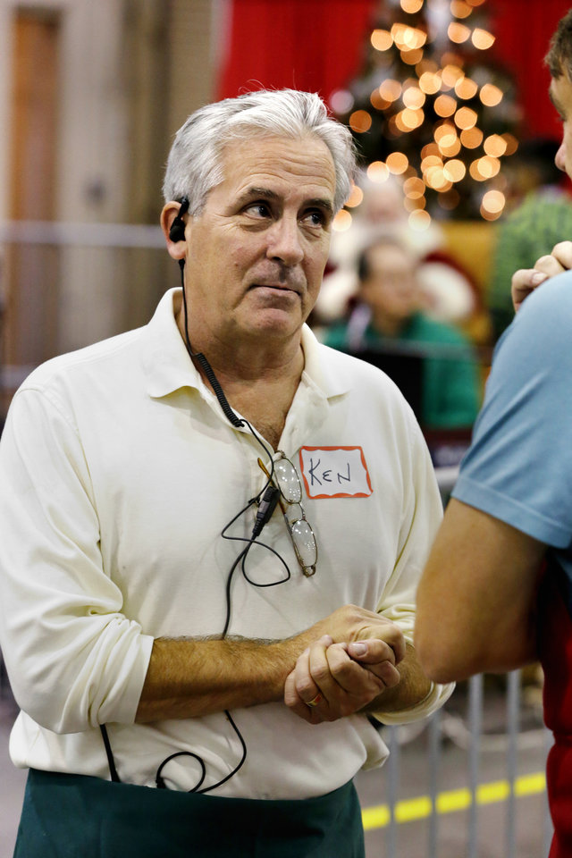 Photo -  Red Andrews Christmas Dinner board member Ken Cassil talks with volunteers at the Cox Convention Center on Sunday. [Photo by Steve Sisney, The Oklahoman]