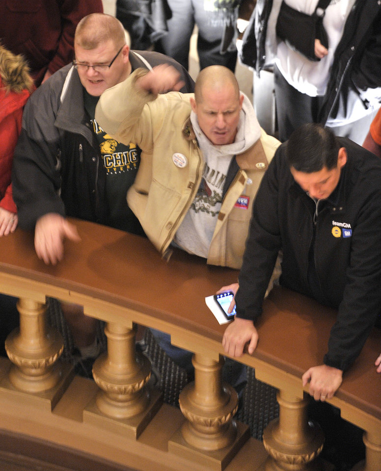 """Trent Mauk of Potterville, Mich., center, pumps his fist and leads some chants as Pro-union demonstrators crowd the Rotunda to chant Wednesday afternoon Dec. 5, 2012, in the Capitol after House and Senate Democrats said there was a possibility of """"Right To Work"""" legislation coming up for a vote.   (AP Photo/Detroit News, Dale G. Young)  DETROIT FREE PRESS OUT; HUFFINGTON POST OUT"""