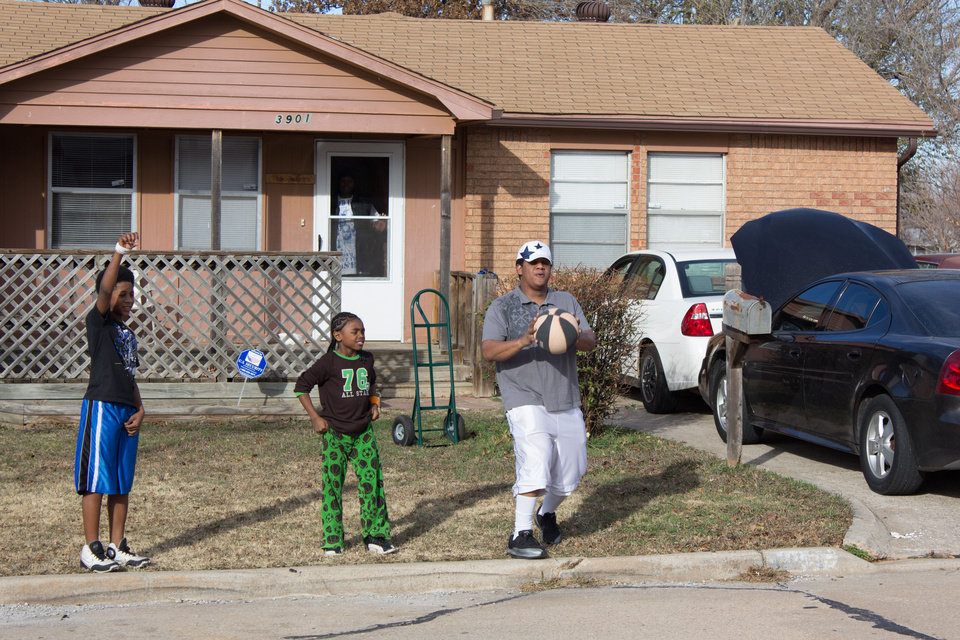Greg Rogers plays ball with his 12-year-old son Elisha (left) and nephew Kaleb Pennon in Del City. Photo by Heather Brown, for The Oklahoman   <strong></strong>