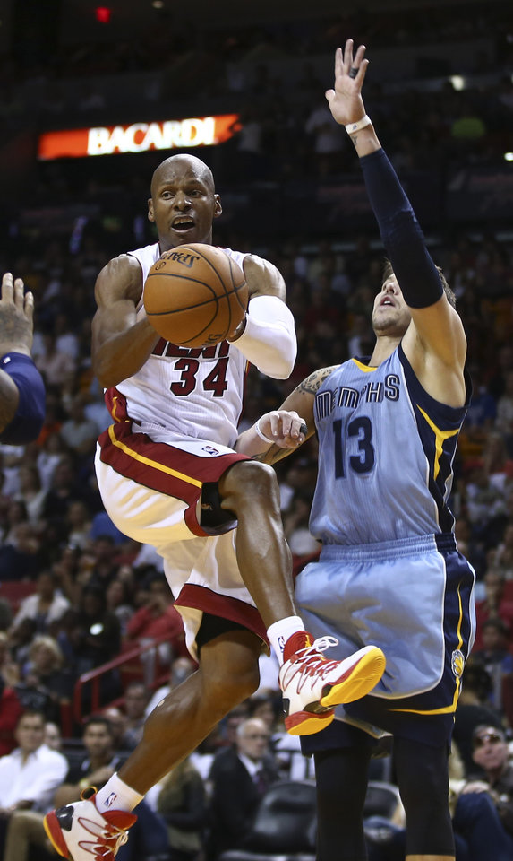 Photo - Memphis Grizzlies' Mike Miller (13) defends MIami Heat's Ray Allen (34) during the first half of an NBA basketball game in Miami, Friday, March 21, 2014. (AP Photo/J Pat Carter)