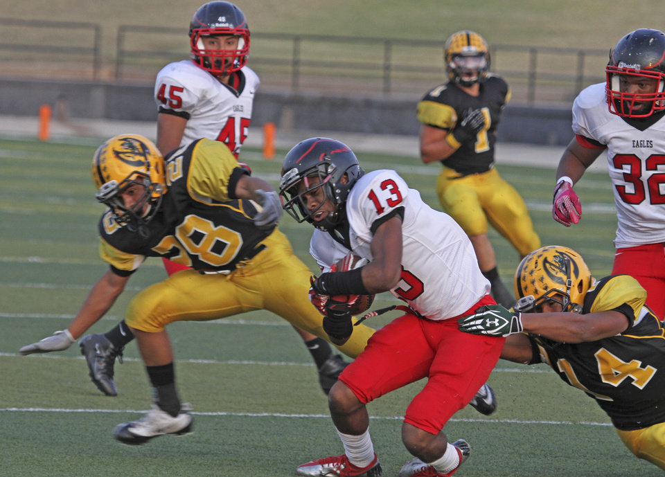 HIGH SCHOOL FOOTBALL: Del City\'s Shawn Epps, center, carries the ball as Lawton MacArthur\'s Adrian Gaines, left, and Miguel Rosario, right, defend during a Sept. 20, 2012, game in Lawton. PHOTO BY BRANDON NERIS, THE LAWTON CONSTITUTION