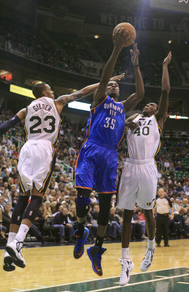 Photo - Oklahoma City Thunder forward Kevin Durant (35) drives to the basket as Utah Jazz's Trey Gilder (23) and Jeremy Evans (40) defends in the second quarter of a preseason NBA basketball game, Friday, Oct. 12, 2012, in Salt Lake City. (AP Photo/Rick Bowmer) ORG XMIT: UTRB108