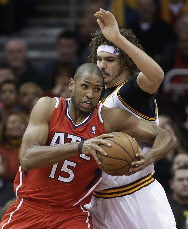 Atlanta Hawks' Al Horford (15) tries to get past Cleveland Cavaliers' Anderson Varejao (17) during the fourth quarter of an NBA basketball game Thursday, Dec. 26, 2013, in Cleveland. Atlanta defeated Cleveland 127-125 in double overtime. (AP Photo/Tony Dejak)
