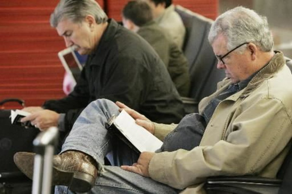 Photo - Mike Brown of Houston,Tx. Reads a book while waiting for his brothers delayed flight to arrive at Will Rogers World Airport Sunday, Dec. 9, 2007. BY JACONNA AGUIRRE