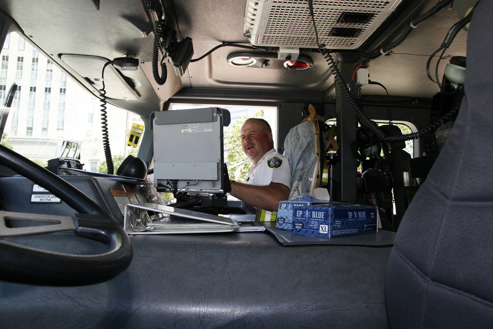 Photo - Battalion Chief Glenn Clark looks at a computer screen in the cab of an Oklahoma City fire truck. Each fire and police unit operated by the city is part of the city's new public safety Wi-Fi network. PROVIDED BY ZACH NASH OF THE CITY OF OKLAHOMA CITY ORG XMIT: 0806032206199976