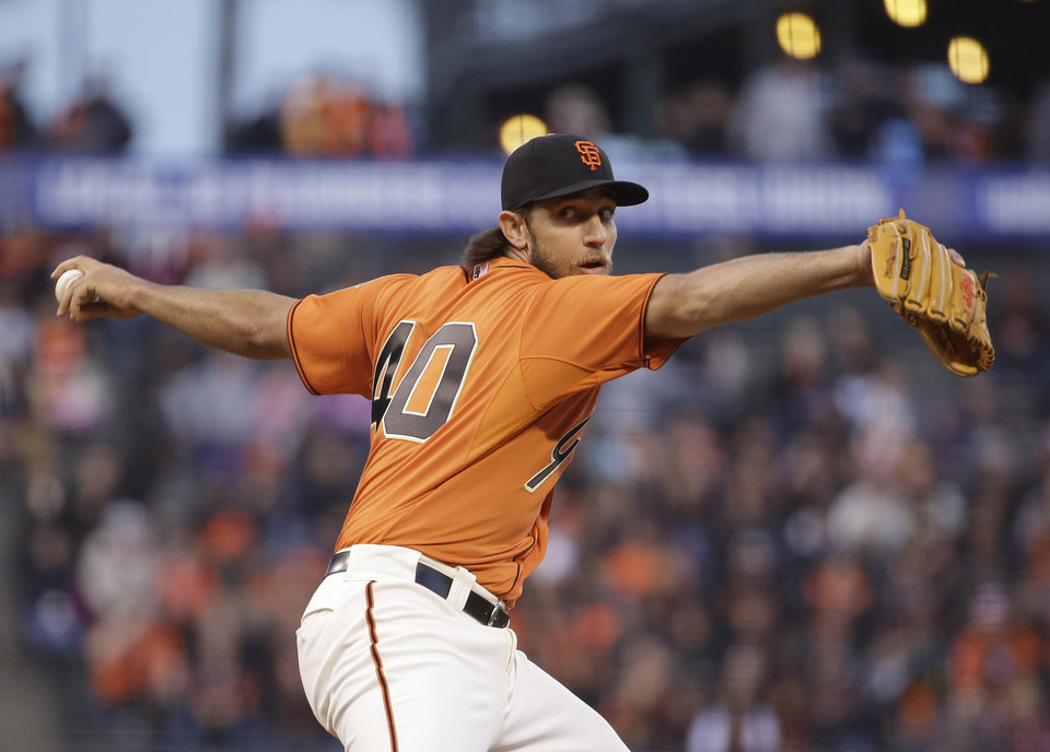 Photo - San Francisco Giants starting pitcher Madison Bumgarner throws in the first inning of a baseball game against the Colorado Rockies Friday, April 11, 2014, in San Francisco. (AP Photo/Eric Risberg)