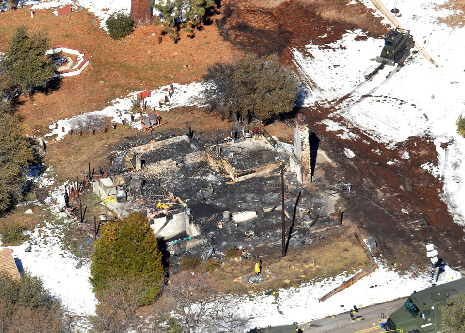 Photo - In this aerial photo, law enforcement authorities investigate the burnt-out cabin Wednesday, Feb.13, 2013, where accused quadruple-murder suspect Christopher Dorner was believed to have died after barricading himself inside, during a Tuesday stand-off with police in the Angeles Oaks area of Big Bear, Calif. San Bernardino Sheriff's Deputy Jeremiah MacKay was killed and another wounded during the shootout with Dorner. (AP Photo/The Sun, John Valenzuela)