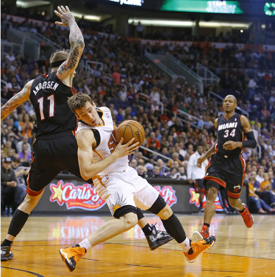 Photo - Phoenix Suns guard Goran Dragic (1)  is fouled by Miami Heat forward Chris Andersen (11) during the first half of an NBA basketball game Tuesday, Feb. 11, 2014, in Phoenix. (AP Photo/The Arizona Republic, David Kadlubowski) MAGS OUT  NO SALES  MESA OUT  MARICOPA COUNTY OUT