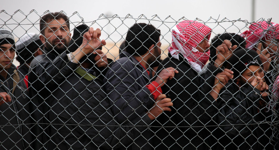 Newly arrived Syrian refugees wait for their turn to receive mattresses, blankets and other supplies, and to be assigned to tents, at the Zaatari Syrian refugees camp in Mafraq, near the Syrian border with Jordan, Monday, Jan. 28, 2013.  UN officials say a spike in Syrian refugees fleeing to Jordan in the past week has seen about 21,000 new arrivals with Jordan's Zaatari refugee camp now hosting about 83,000 registered refugees.  (AP Photo/Mohammad Hannon)