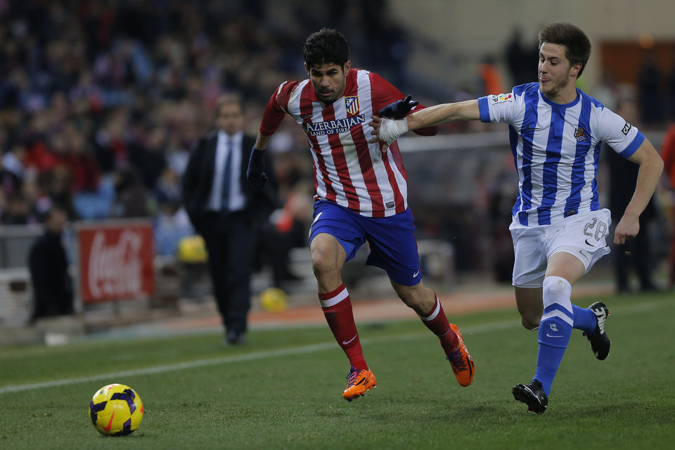 Photo - Atletico's Diego Costa, left, in action with Real Sociedad's Jon Gaztanaga, right,  during a Spanish La Liga soccer match between Atletico de Madrid and  Real Sociedad at the Vicente Calderon stadium in Madrid, Spain, Sunday, Feb. 2, 2014. (AP Photo/Andres Kudacki)