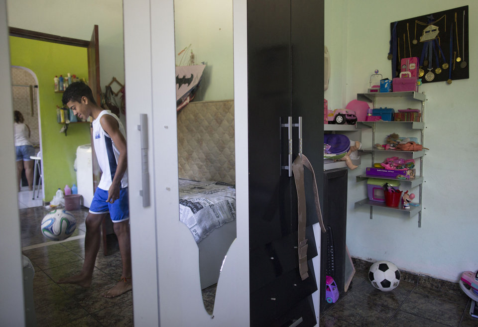 Photo - In this June 17, 2014 photo, Andre Rodrigues de Principe, 14, known as Andrezinho to his neighbors, controls the ball in his bedroom in the Vidigal slum of Rio de Janeiro, Brazil. For every player who makes it to a first division team, thousands are left behind, according to the University of Football, a group that seeks to use the sport to promote Brazil's development.  (AP Photo/Leo Correa)