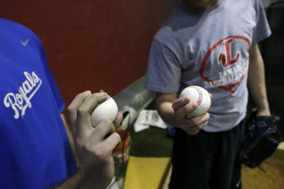 Photo - In this Feb. 24, 2014 photo, Kansas City Royals minor league pitcher John Walter, left, of Haddonfield, N.J., demonstrates a pitch as he instructs Steve Cocotoni, 15, at Power Train Sports Institute's AFC Baseball & Softball Academy in Cherry Hill, N.J.  (AP Photo/Mel Evans)