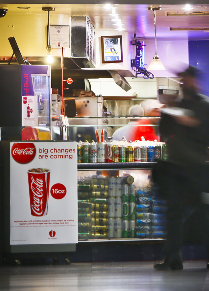 Photo - FILE - In this March 8, 2013 file photo, a Coca-Cola poster about the city's anticipated beverage ban is displayed at a pizza shop at New York's Penn Station.  New York City's groundbreaking limit on the size of sugar-laden drinks has been struck down by a judge shortly before it was set to take effect. The restriction was supposed to start Tuesday, March 12, 2013. The rule prohibits selling non-diet soda and some other sugary beverages in containers bigger than 16 ounces. It applies at places ranging from pizzerias to sports stadiums, though not at supermarkets or convenience stores. (AP Photo/Bebeto Matthews)
