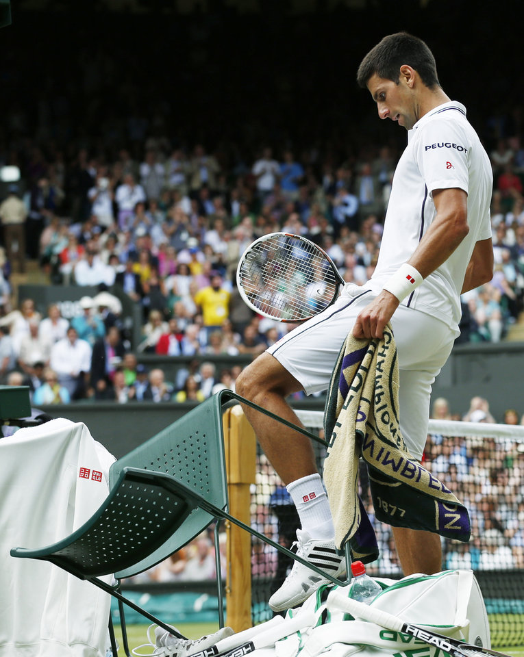 Photo - Novak Djokovic of Serbia knocks over his chair at a change of ends as he plays against Roger Federer of Switzerland during their men's singles final match at the All England Lawn Tennis Championships in Wimbledon, London, Sunday, July 6, 2014. (AP Photo/Sang Tan, Pool)
