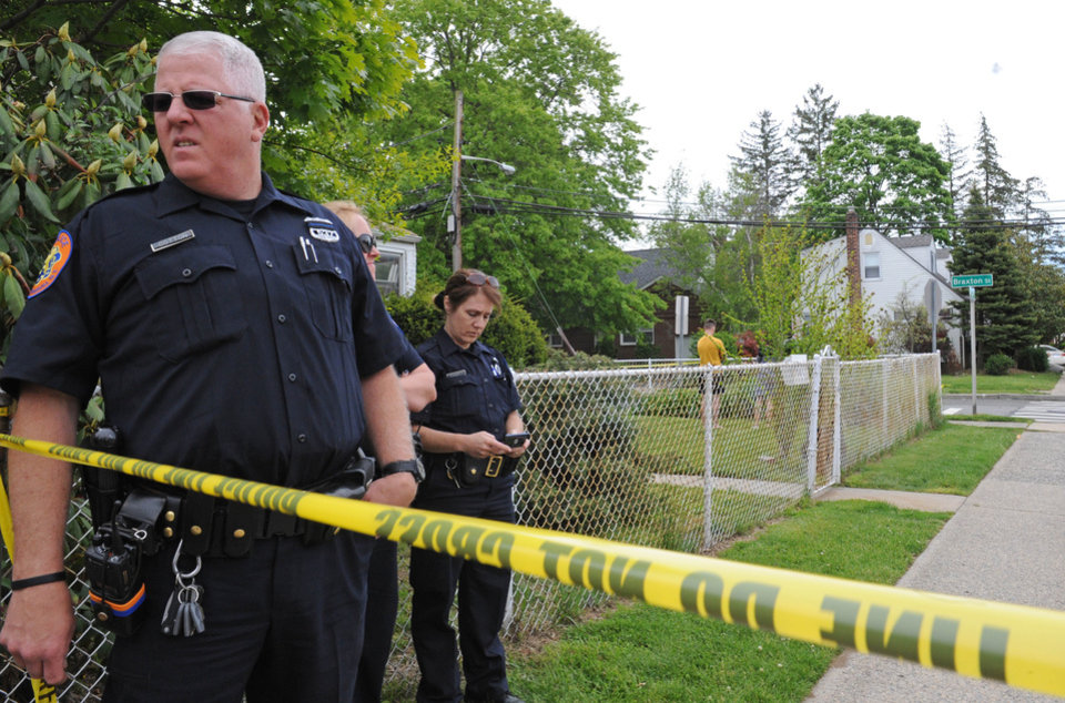 Officers guard the area leading to the house, background right, where a Hofstra University student and an armed intruder were killed during an overnight break-in, next to the campus, Friday, May 17, 2013, in Uniondale, N.Y. (AP Photo/ Louis Lanzano)