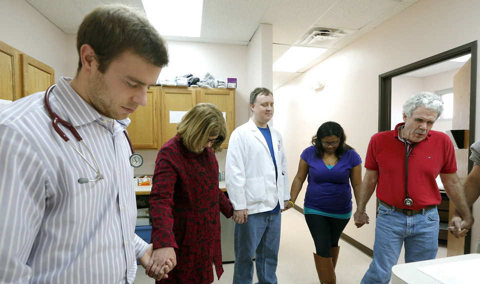 Photo - Benjamin McKinney; Ellen Ingram, Good Shepherd MInistries director of development; Stephen Huggins, Leah Thompson and Dr. Fred Loper pray before opening the Good Shepherd Ministries free clinic in Oklahoma City. Photo by Sarah Phipps, The Oklahoman   SARAH PHIPPS - SARAH PHIPPS