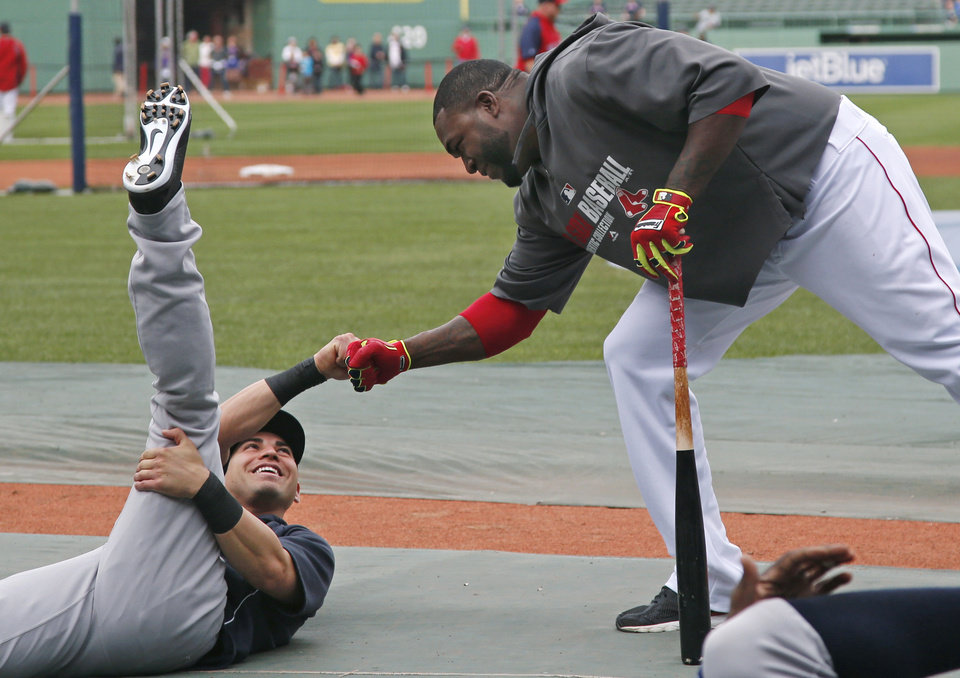 Photo - Boston Red Sox's David Ortiz, right, reaches down to greet a former teammate, New York Yankees' Jacoby Ellsbury, prior to a baseball game at Fenway Park in Boston, Tuesday, April 22, 2014. (AP Photo/Elise Amendola)