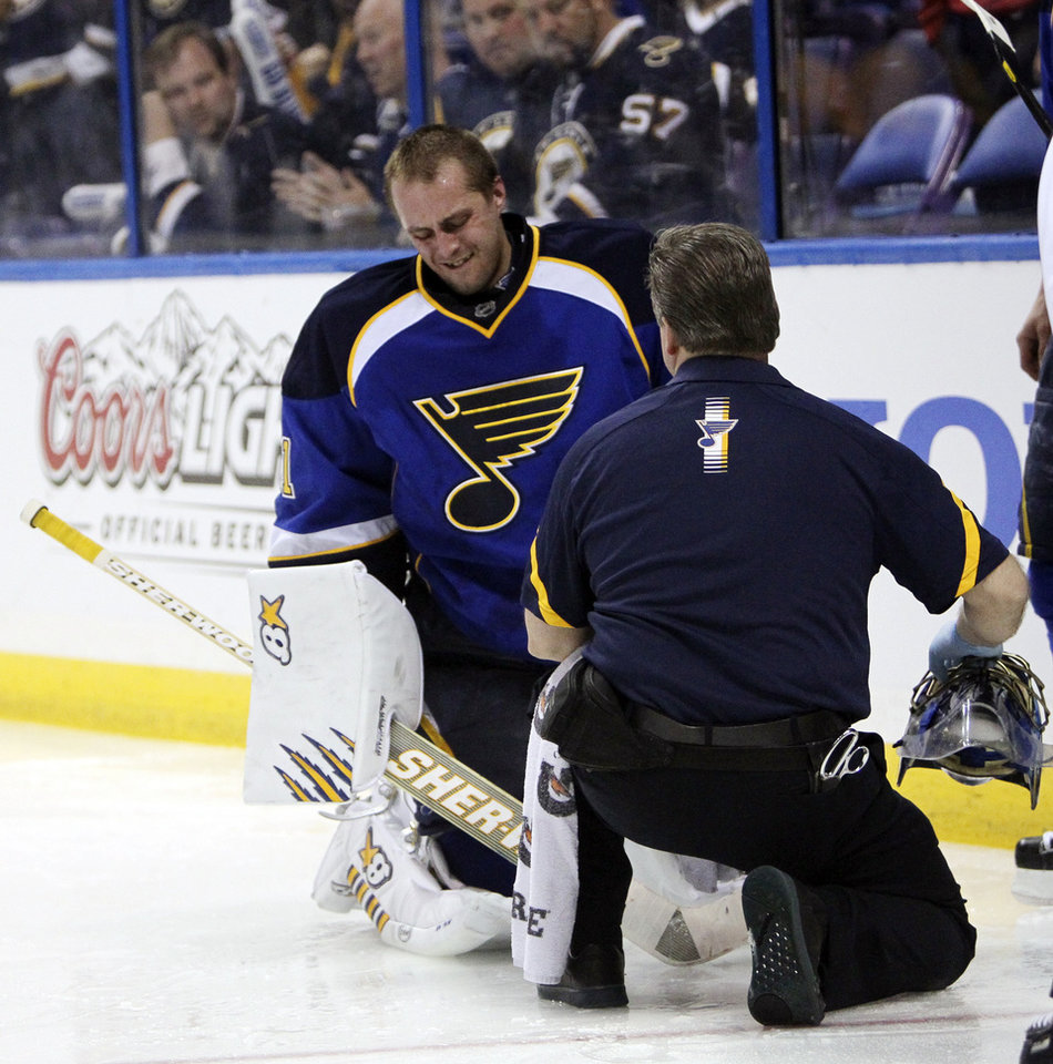 Photo -   St. Louis Blues goaltender Jaroslav Halak is tended to by trainer Ray Barile after he collided with Barret Jackman against the San Jose Sharks during the second period in Game 2 of an NHL Stanley Cup first-round hockey playoff series Saturday, April 14, 2012, in St. Louis. The Blues won 3-0. (AP Photo/St. Louis Post-Dispatch, Chris Lee) EDWARDSVILLE INTELLIGENCER OUT; THE ALTON TELEGRAPH OUT