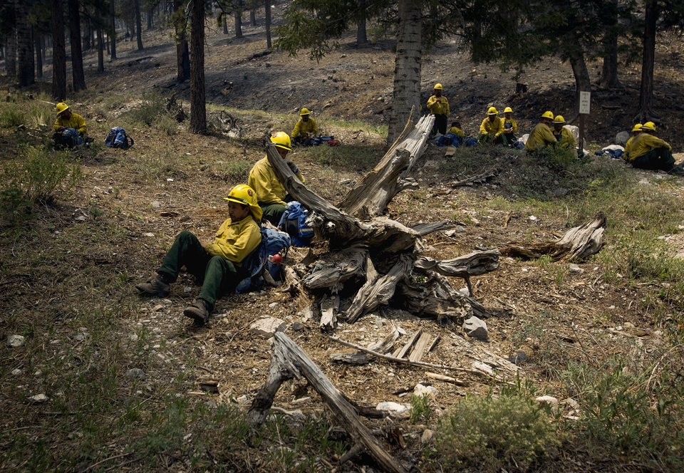 Photo - A Type 2 firefighters from Sequoia National Forest take a break from the Carpenter 1 Fire at the Rainbow subdivision on Mt. Charleston near Las Vegas on Tuesday, July 9, 2013. The lightning-caused fire, which started on July 1, has burned nearly 20,000 acres. Over 800 firefighters are working the blaze  in the Spring Mountains National Recreation Area. (AP Photo/Las Vegas Review-Journal, Jeff Scheid)