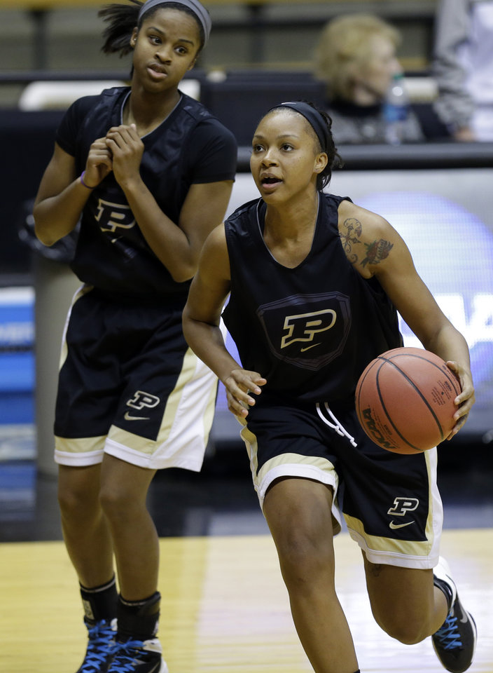 Photo - Purdue guard Dee Dee Williams, right, drives in front of teammate April Wilson during practice at the NCAA women's college basketball tournament in West Lafayette, Ind., Friday, March 21, 2014.  Purdue plays Akron in a first-round game on Saturday. (AP Photo/Michael Conroy)