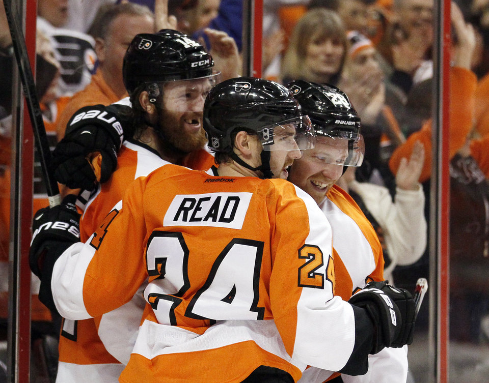 Photo - Philadelphia Flyers' Mattt Read, center, celebrates his goal along with teammates Sean Couturier, left, and Claude Giroux  during the second period of an NHL hockey game against against the Pittsburgh Penguins, Saturday, March 15, 2014, in Philadelphia. (AP Photo/Tom Mihalek)
