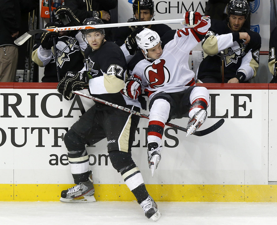 Photo - New Jersey Devils' David Clarkson (23) is checked into the bench by Pittsburgh Penguins' Simon Despres (47) during the first period of an NHL hockey game, Saturday, Feb. 2, 2013, in Pittsburgh. (AP Photo/Keith Srakocic)