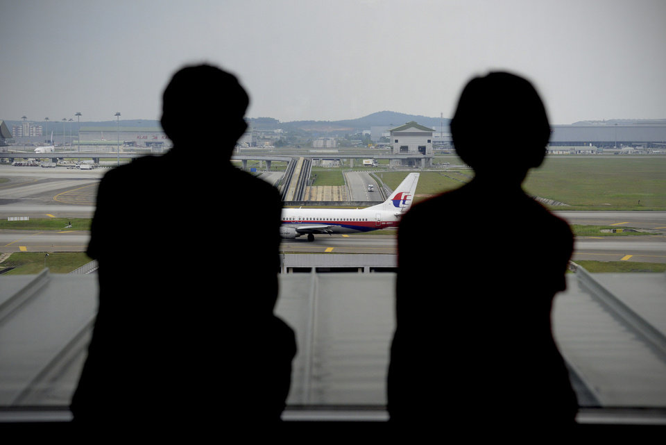 Photo - A couple is silhouetted as they watch a Malaysia Airlines plane on the tarmac from the viewing gallery at Kuala Lumpur International Airport in Sepang, Malaysia, Thursday, April 10, 2014. With hopes high that search crews are zeroing in on the missing Malaysian jetliner's crash site, ships and planes hunting for the aircraft intensified their search efforts on Thursday after equipment picked up sounds consistent with a plane's black box in the deep waters of the Indian Ocean. (AP Photo/Joshua Paul)