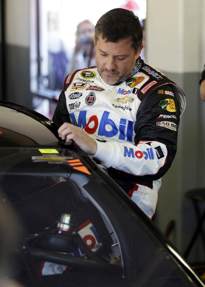 Photo - Driver Tony Stewart climbs in his car before practice for the NASCAR Sprint Unlimited auto race at Daytona International Speedway in Daytona Beach, Fla., Friday, Feb. 14, 2014.  Stewart has not raced in more than six months since he broke two bones in his leg in an August 2013 sprint-car crash.(AP Photo/John Raoux)