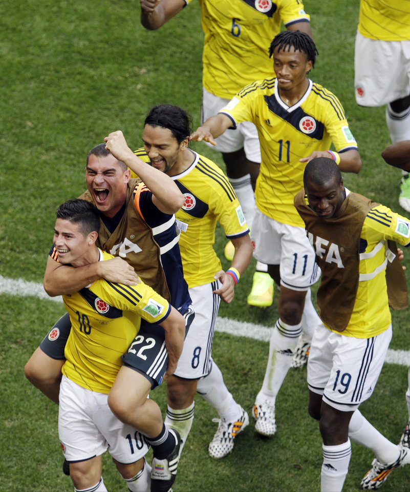 Photo - Colombia's James Rodriguez, left, celebrates with teammate  goalkeeper Faryd Mondragon during the group C World Cup soccer match between Colombia and Ivory Coast at the Estadio Nacional in Brasilia, Brazil, Thursday, June 19, 2014.  (AP Photo/Themba Hadebe)