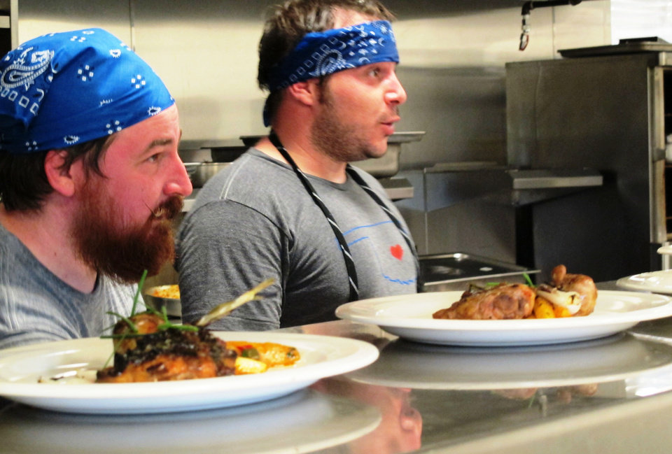 Photo - Chefs Josh Valentine, left, and David Henry try to stay cool on the line during Sunday's portion of the OK Chefs Relief Pop-Up Restaurant in the Myriad Botanicals Gardens event space. All proceeds were donated to the Oklahoma Chapter of the American Red Cross.  DAVE CATHEY - THE OKLAHOMAN