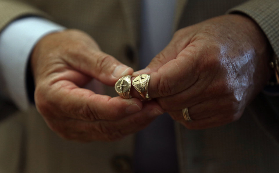 In this Friday, Aug. 16, 2013 photo taken in Raleigh, N.C., David Cox Jr. holds a pair of gold aviator rings, one of which is a replica, right, of the original ring, left, that belonged to his father, U.S. Army Air Corps 2nd Lt. David C. Cox who traded the ring for a couple of chocolate bars while he was imprisoned in a German prisoner of war camp during World War II. The ring was returned by a German couple through some investigative help from an American neighbor. (AP Photo/Gerry Broome)