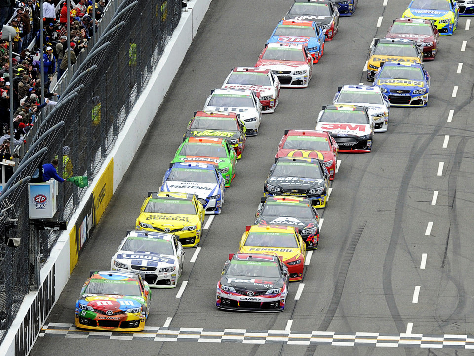 Photo - Driver Kyle Busch (18) leads the field to the green flag for the start of a NASCAR Sprint Cup Series auto race at Martinsville Speedway, Sunday, March 30, 2014, in Martinsville, Va. (AP Photo/Mike McCarn)