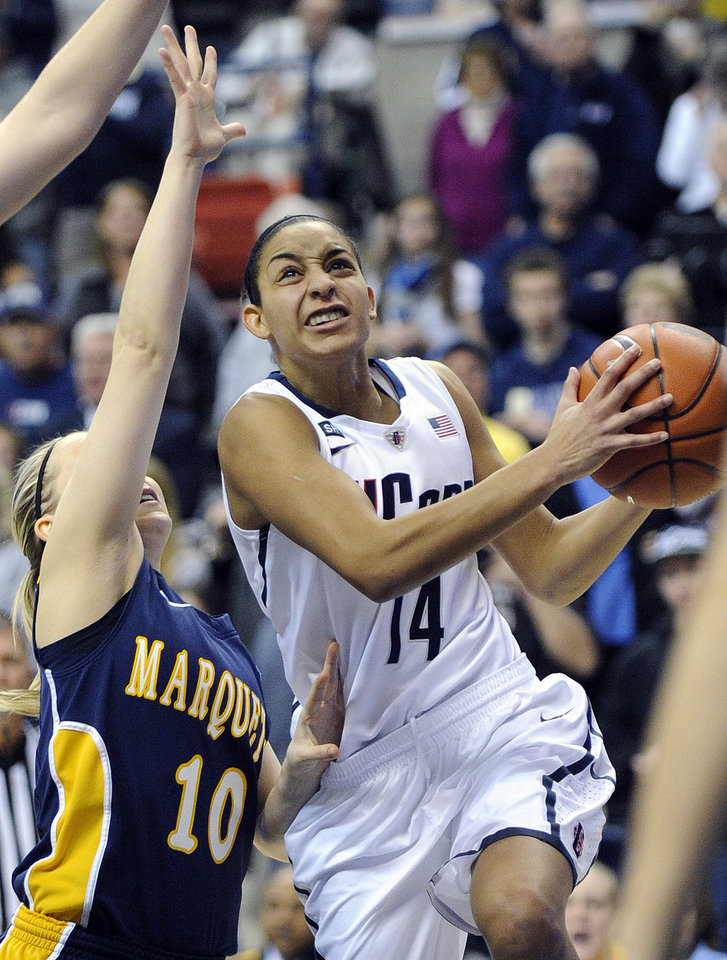 Photo - Connecticut's Bria Hartley, right, drives past Marquette's Brooklyn Pumroy during the first half of an NCAA college basketball game in Storrs, Conn., Tuesday, Feb. 5, 2013. (AP Photo/Fred Beckham)