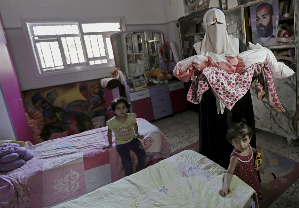 Photo - A Palestinian relative carries the body of 18-month-old Zainah Abu Taqiya, who was killed Sunday morning in an Israeli strike on a building, during her funeral in Gaza, northern Gaza Strip, Sunday, Aug. 24, 2014. Several people were killed including the baby Zainah in an airstrike on an apartment building in Sheikh Ridwan, a district of Gaza City located nearly 3 kilometers (almost 2 miles) northwest of the city center, according to Gaza health official Ashraf al-Kidra. (AP Photo/Adel Hana)