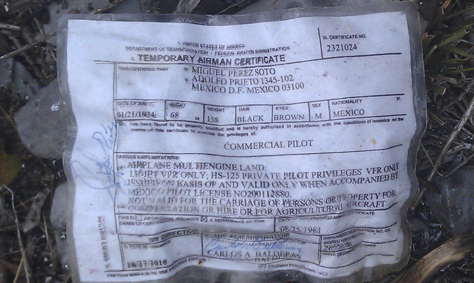 A temporary airman\'s certificate issued by the Federal Aviation Administration (FAA) sits on the ground at the site where a plane carrying U.S. born singer Jenni Rivera apparently crashed near Iturbide, Mexico, Sunday, Dec. 9, 2012. The wreckage of a small plane believed to be carrying Rivera, the singer whose soulful voice and unfettered discussion of a series of personal travails made her a Mexican-American superstar, was found in northern Mexico on Sunday. Authorities said there were no survivors. (AP Photo)
