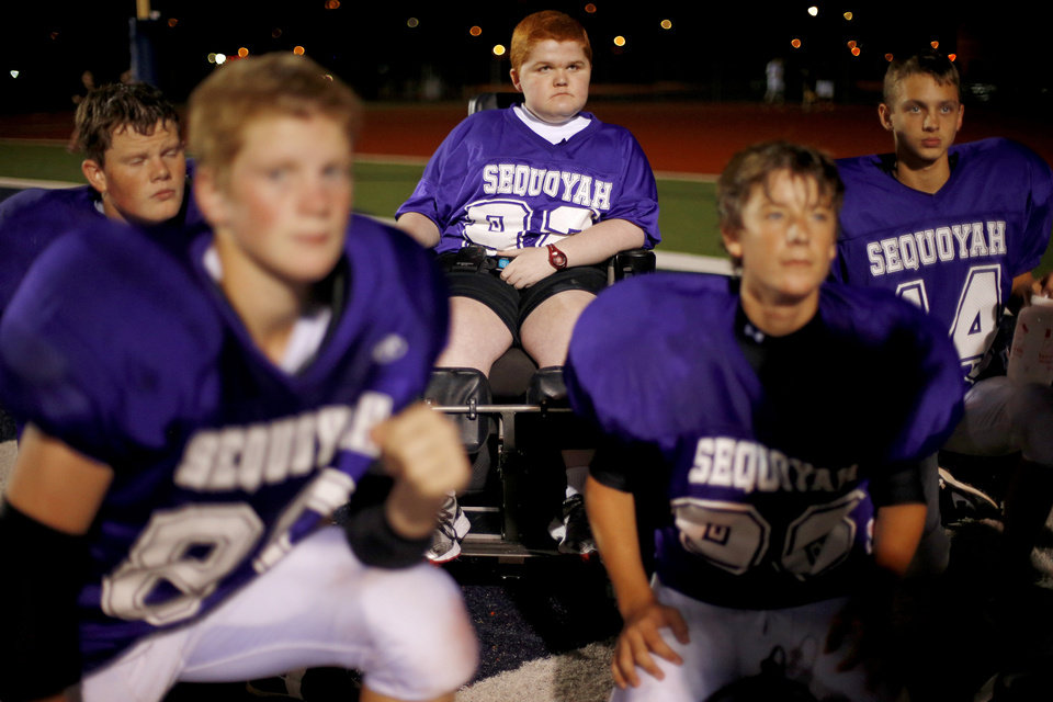 Photo - Keegan Erbst listens to the coaches during halftime of Sequoyah Middle School football game, Thursday, September 27, 2012. Keegan, who has muscular dystrophy and is confined to a wheelchair, got involved with the team after players Lucas Coker, James Colton, and Parker Tumleson, pushed suggested it to the coach.  Photo by Bryan Terry, The Oklahoman