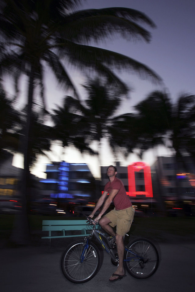 FILE - In this Jan. 31, 2007 file photo, a man rides a bike in the South Beach area of Miami Beach, Fla. The bike scene in Miami has taken off in recent years, and since parking is expensive and can be hard to find, riding a bike can be a great way to get around. (AP Photo/Carlo Allegri, File)
