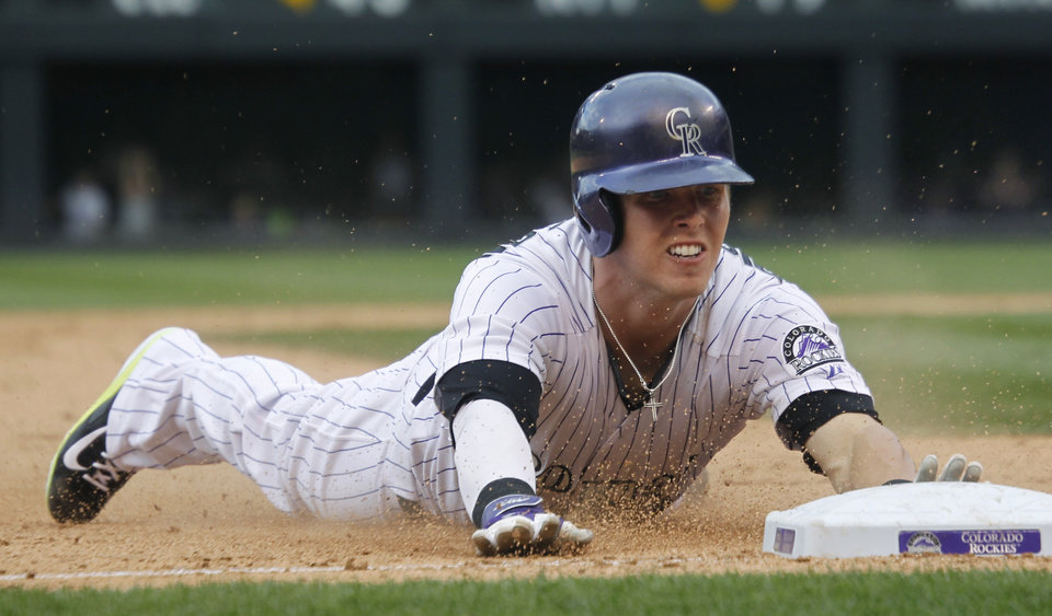 Photo - Colorado Rockies' Corey Dickerson slides safley into third base with a triple against the Milwaukee Brewers in the ninth inning of the Brewers' 6-5 victory in a baseball game in Denver on Sunday, June 22, 2014. When the throw was mishandled by Brewers fielders, Dickerson tried to score from third base but stumbled and was then easily tagged out at home plate. (AP Photo/David Zalubowski)