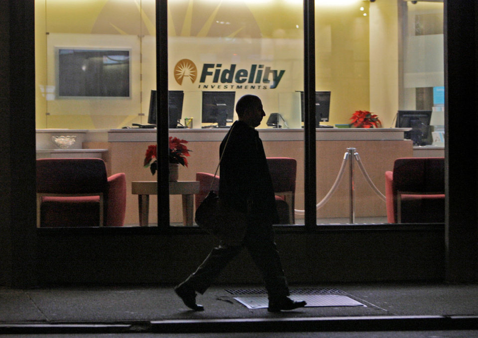 Photo - FILE - In this Thursday, Dec. 4, 2008 file photo, a man walks past a Fidelity Investments office in the Financial District of downtown Boston. On Wednesday, Oct. 9, 2013, the nation's largest manager of money market mutual funds said that it no longer holds any U.S. government debt that comes due around the time the nation could hit its borrowing limit. Money market portfolio managers at Fidelity Investments have been selling off their government debt holdings over the last couple of weeks, said Nancy Prior, president of Fidelity's Money Market Group. While Fidelity expects the debt ceiling issue to be resolved, the Boston-based asset manager said it is taking steps to protect investors. (AP Photo/Charles Krupa)